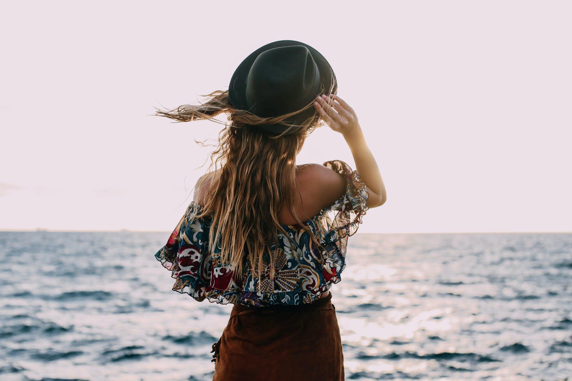 stylish woman enjoying windy day on coast